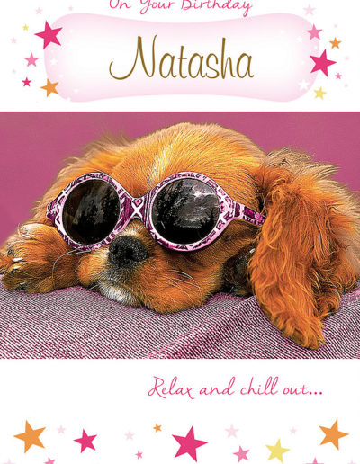 A cute Birthday Card, with a dark pink background, showing a cute puppy with long hairy ears wearing big round pink-framed sunglasses